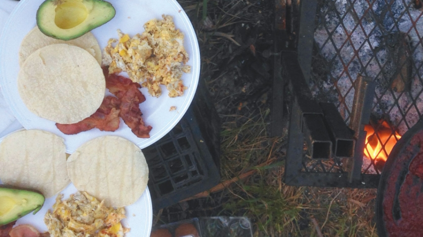 plate of avocado, bacon, tortillas, and eggs at a campsite