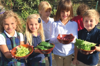 students with fresh harvest of lettuce