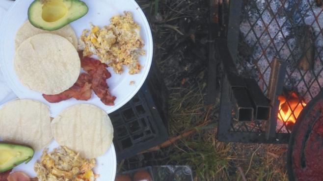 plate of avocado, bacon, tortillas, and eggs at a campsite