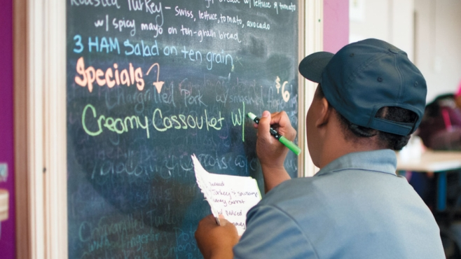 man writing specials on board